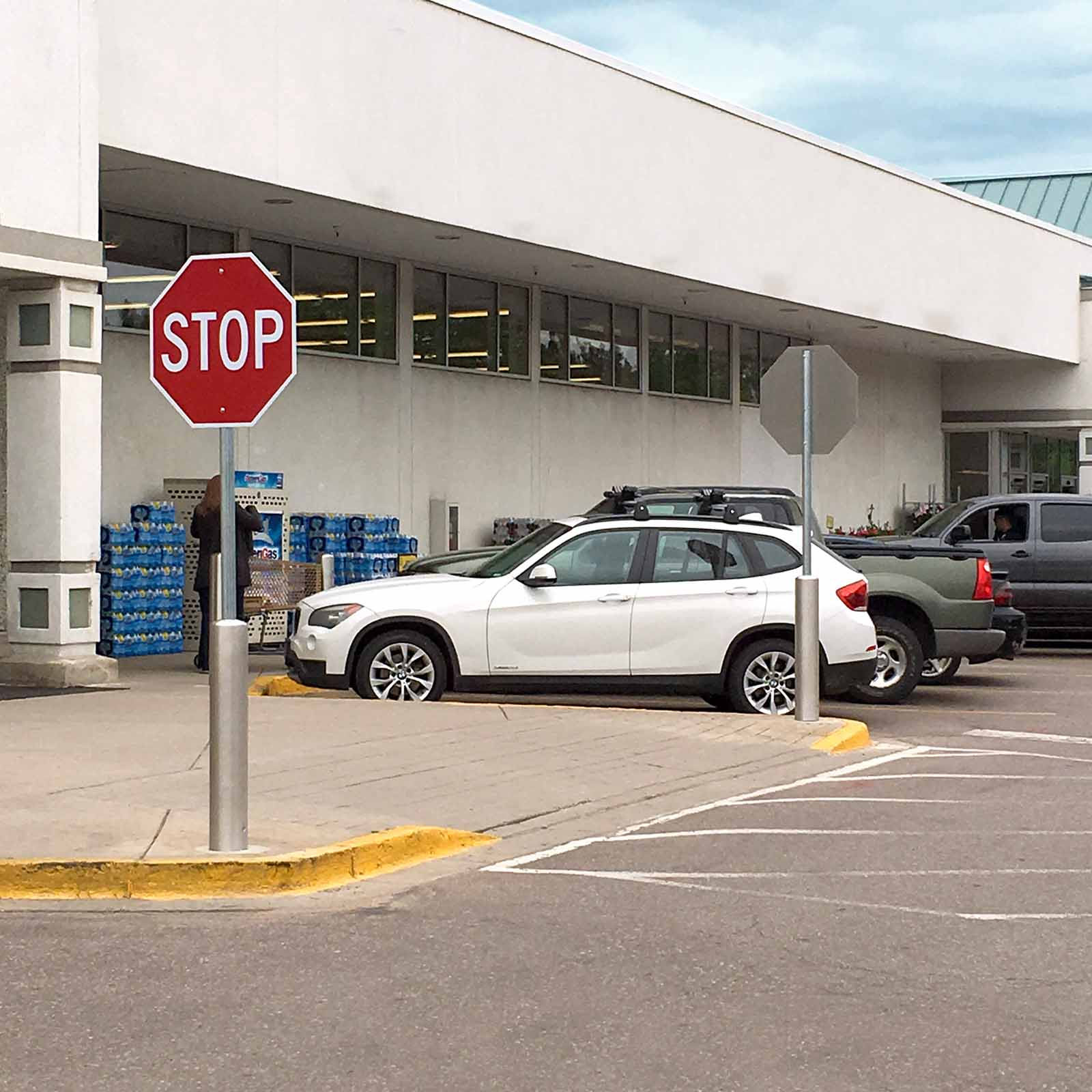McCue Crash Tested ASTM F3016 CrashCore Bollard with Sign Post in parking lot